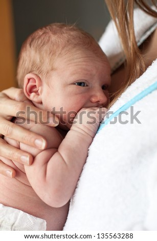 Closeup of newborn baby boy in mother's arms - stock photo