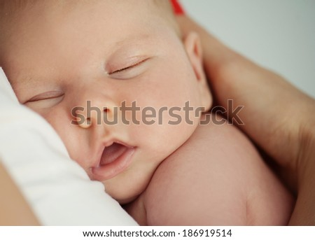 Closeup of newborn baby boy sleeping on his mother�´s chest - stock photo