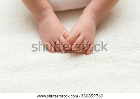 Closeup of newborn baby feet lying on towel - stock photo