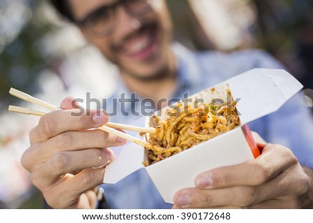 Closeup of noodles in a  take away box, man holding them with chopsticks. - stock photo