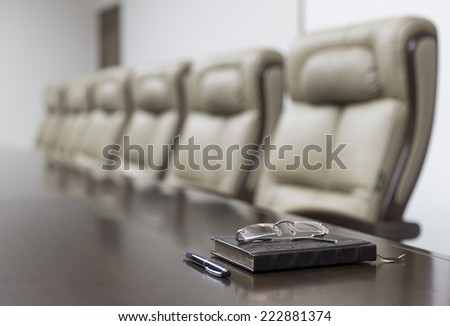 Closeup of notebook on table in empty corporate conference room before business meeting in office - stock photo