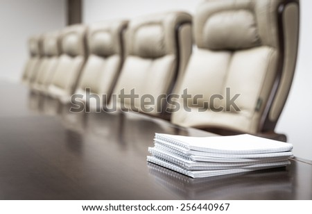 Closeup of notebooks on table in empty corporate conference room before business meeting in office