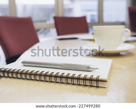 Closeup of notepad in conference modern style room interior. Agenda on table with coffee in empty corporate conference room. - stock photo