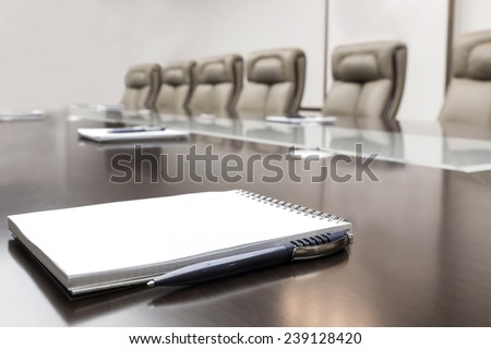 Closeup of notepad kept on table in empty conference room - stock photo