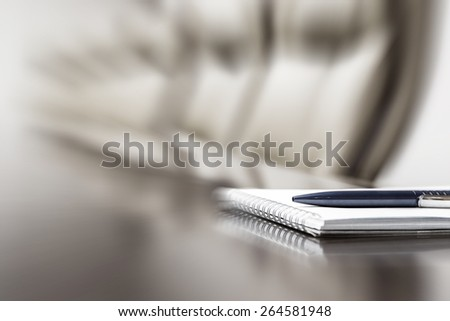 Closeup of notepad kept on table in empty conference room, motion blur - stock photo