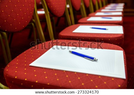 Closeup of notepad with pen for agenda on chairs in empty corporate conference room before business meeting - stock photo
