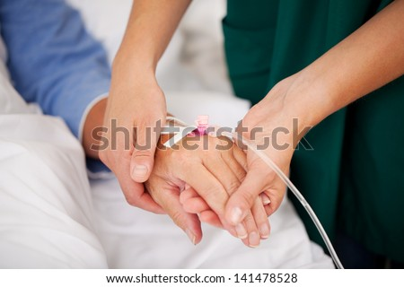 Closeup of nurse holding patients hand in hospital - stock photo