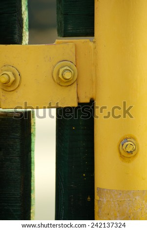 Closeup of nuts and yellow metal bar