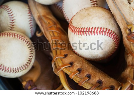 closeup of old baseballs and gloves in metal bucket, used for practice