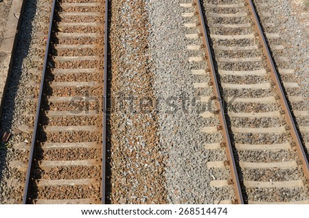 closeup of old industrial railway tracks with gravel and stones - stock photo