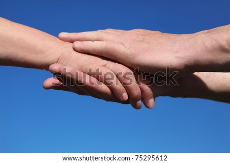 closeup of old man holding hand of old woman for two hands, blue sky