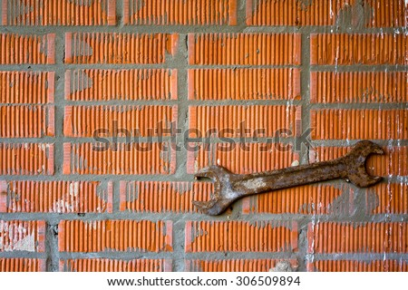 Closeup of old open-end wrench hand tool rusted with age Vintage Hand Tool on the a bright brick wall - stock photo