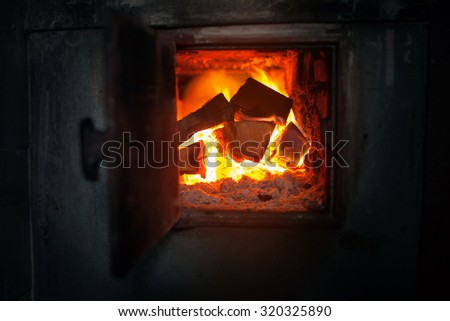 closeup of old rural wood stove with the burning firewood. Alternative energy source background - stock photo