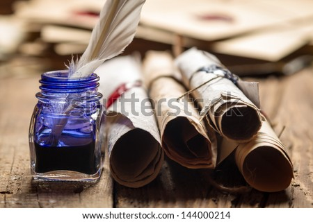 Closeup of old scrolls and blue ink in the inkwell - stock photo