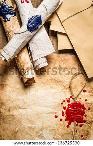 Closeup of old scrolls and sealing wax on wooden table - stock photo
