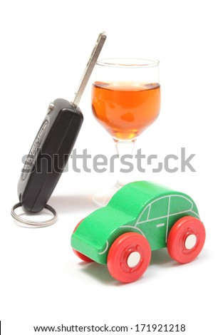 Closeup of old wooden toy car, glass of wine and car key, key car and alcohol, don't drink and drive concept. Isolated on white background