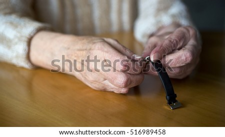 closeup of old wrinkled female hands setting the time on her wristwatch