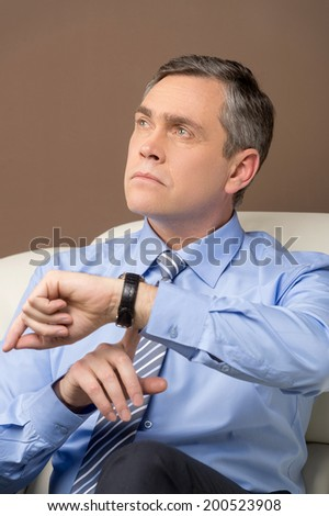 closeup of older man looking at watch. portrait of businessman sitting at sofa and thinking - stock photo