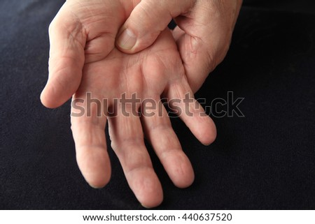Closeup of older man with painful palm on black background - stock photo