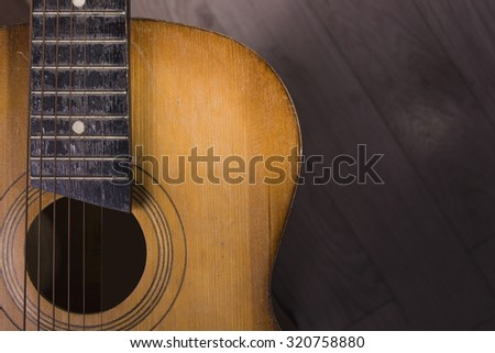 Closeup of one acoustic string light brown color wooden musical instrument of guitar with beautiful shape indoor in studio on wooden backdrop copyspace, horizontal picture - stock photo