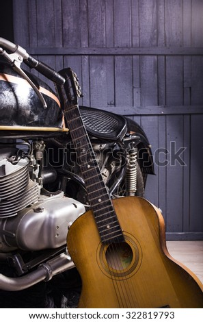 Closeup of one acoustic string light brown color wooden musical instrument of guitar with beautiful shape indoor in studio standing near chrome bike on gery wooden backdrop, vertical picture