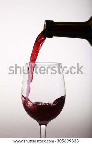 Closeup of one beautiful clear glass goblet with pouring from green bottle tasty sweet red dessert grape wine with bubbles in standing position isolated on white studio background, vertical picture