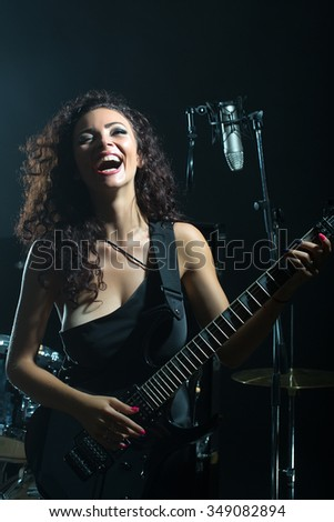 Closeup of one beautiful emotional expressive cool young brunette sexual rock musician woman with long curly hair sitting in recording studio playing electro guitar singing near drums and microphone