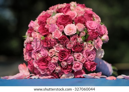 Closeup of one big beautiful colorful soft aroma fresh wedding bouquet of many pink and purple rose flowers lying sunny day outdoor on natural background, horizontal picture - stock photo