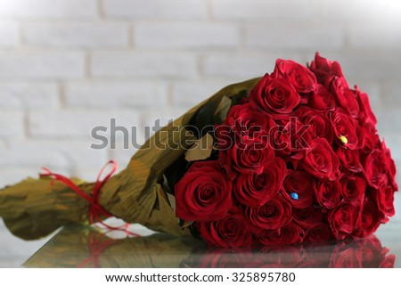 Closeup of one big beautiful colorful soft aroma fresh wedding or birthday bouquet of many red rose flowers lying sunny day outdoor on natural background, horizontal picture - stock photo