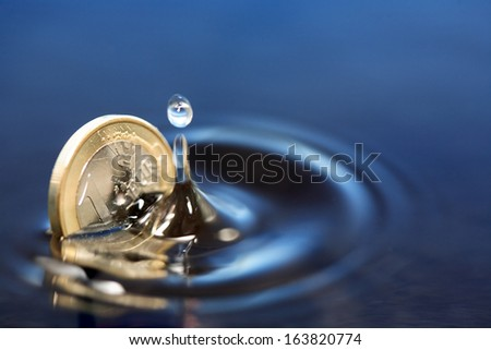 Closeup of one euro coin sinking in water with splash - stock photo