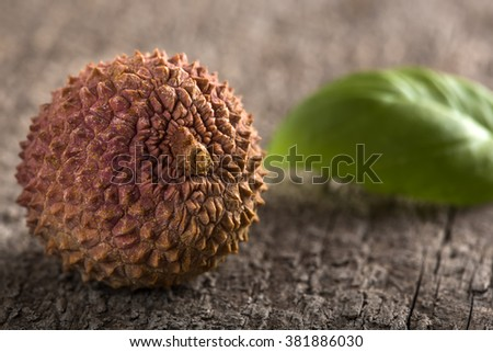 Closeup of one fresh Lychee on wood table - stock photo