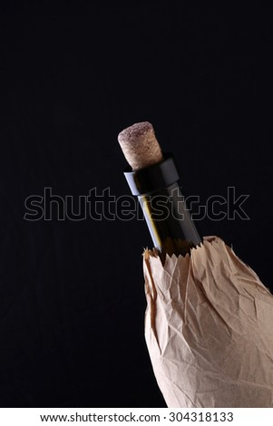 Closeup of one glass green wine corked bottle with alcohol beverage with cork in brown paper packet isolated on black studio background copyspace, vertical picture