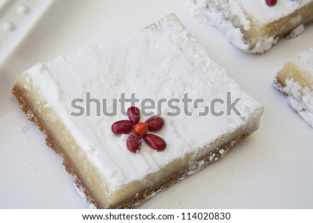 Closeup of one lemon bar with red candy flower accent placed on white glass tray.