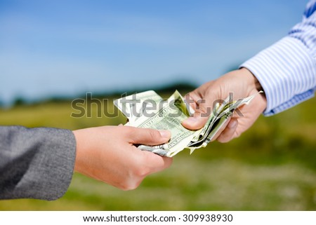 Closeup of one person's hand giving some money to another peron on countryside blurred background