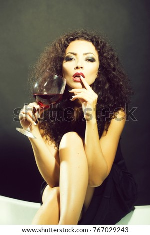 Closeup of one pretty sensual mysterious young brunette sexy woman with long curly hair and bright makeup in dress sitting in studio drinking red wine from glass on black background, vertical picture