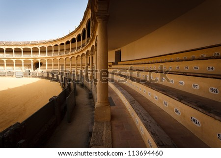 Closeup of open bench seating and safety ring at empty bullfight arena in Ronda, Spain