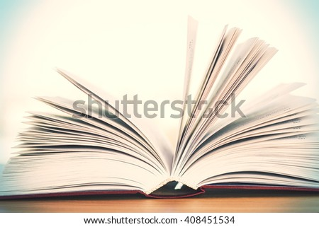 Closeup of open book on wooden table