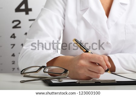 Closeup of ophthalmologist's hands writing a prescription - stock photo