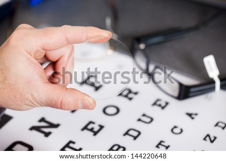 Closeup of optician's hand holding lens against Snellen chart - stock photo