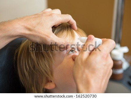 Closeup of optometrist hands putting eye drops in patients eye in clinic - stock photo