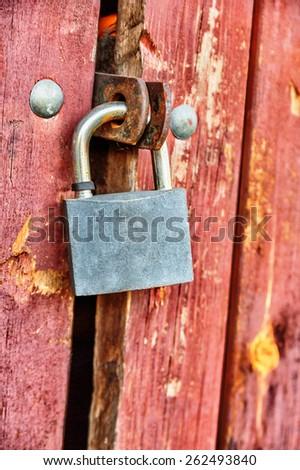 Closeup of padlock closed on wooden door - stock photo