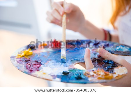 Closeup of paintbrush in woman hands mixing paints on palette - stock photo