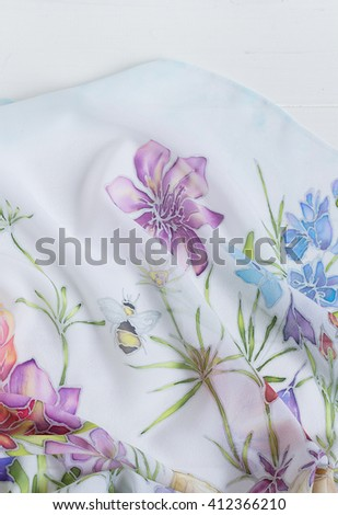 Closeup of painted batik with summer floral pattern. Handmade painting on silk. Shallow focus