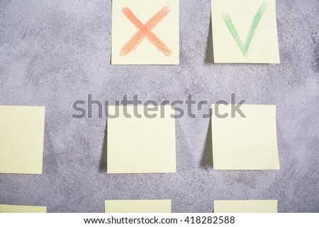 Closeup of paper stickers with red cross and green tick glued onto grey concrete wall - stock photo