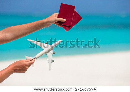 Closeup of passports and white airplane background the sea - stock photo