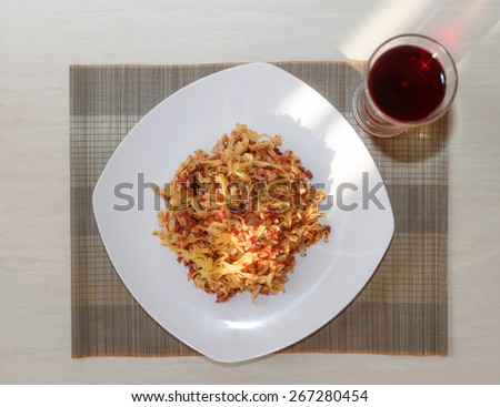 Closeup of pasta with fried meat on white plate and glass of juice, top view - stock photo