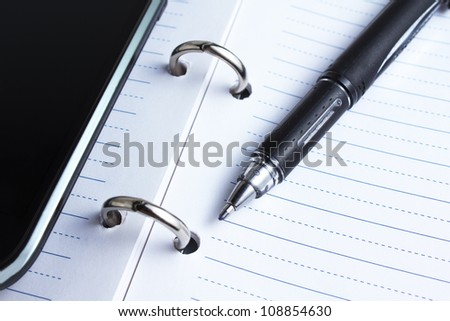 closeup of pen, notebook and cell phone