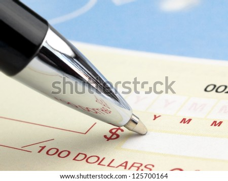 Closeup of Pen on the Cheque - stock photo