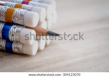 Closeup of pencil and eraser on wooden table - stock photo