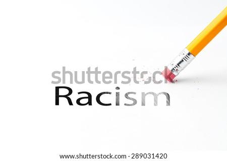 Closeup of pencil eraser and black racism text. Racism. Pencil with eraser. - stock photo